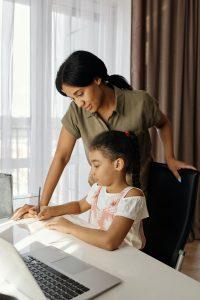 Parent helping child through remote instruction